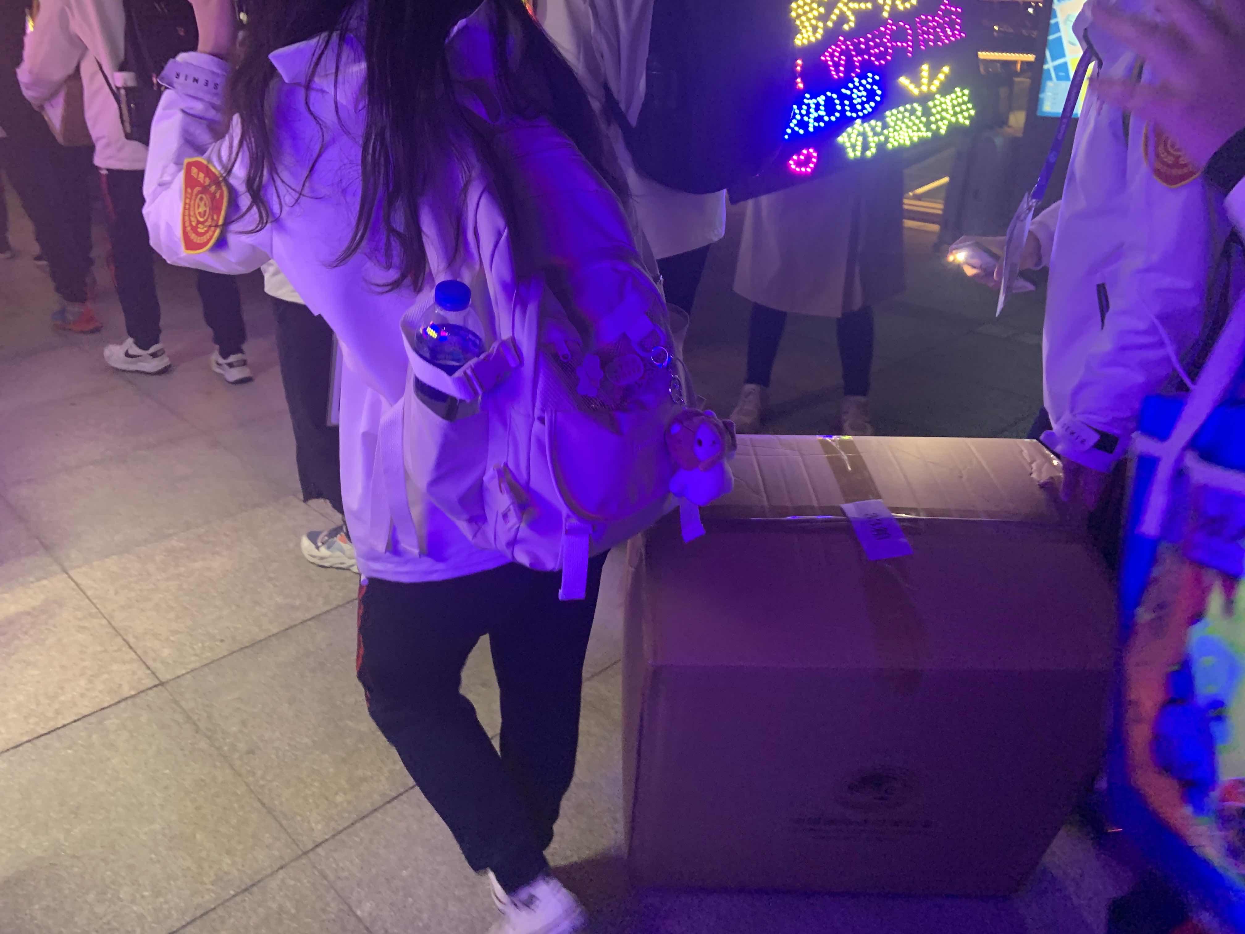 不少同学抬着用纸箱装的行李